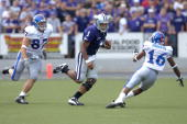 Quarterback Josh Freeman of the Kansas State Wildcats rushes up field against pressure from defenders John Larson and Chris Harris of the Kansas...
