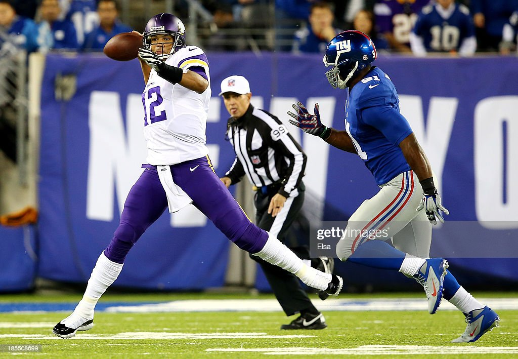 Quarterback Josh Freeman #12 of the Minnesota Vikings scrambles as defensive end Justin Tuck #91 of the New York Giants defends during a game at MetLife Stadium on October 21, 2013 in East Rutherford, New Jersey.