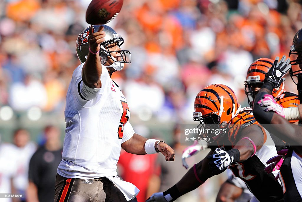 Quarterback <a gi-track='captionPersonalityLinkClicked' href=/galleries/search?phrase=Josh+Freeman&family=editorial&specificpeople=4036797 ng-click='$event.stopPropagation()'>Josh Freeman</a> #5 of the Tampa Bay Buccaneers gets off a pass as he is pressured by the Cincinnati Bengals defense at Paul Brown Stadium on October 10, 2010 in Cincinnati, Ohio.
