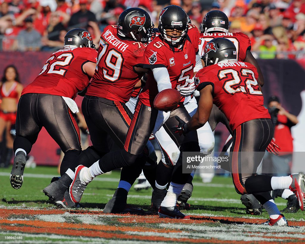 Quarterback <a gi-track='captionPersonalityLinkClicked' href=/galleries/search?phrase=Josh+Freeman&family=editorial&specificpeople=4036797 ng-click='$event.stopPropagation()'>Josh Freeman</a> #5 of the Tampa Bay Buccaneers hands off to running back <a gi-track='captionPersonalityLinkClicked' href=/galleries/search?phrase=Doug+Martin+-+American+Football+Running+Back&family=editorial&specificpeople=9693143 ng-click='$event.stopPropagation()'>Doug Martin</a> #22 against the Atlanta Falcons November 25, 2012 at Raymond James Stadium in Tampa, Florida. The Falcons won 24 - 23.
