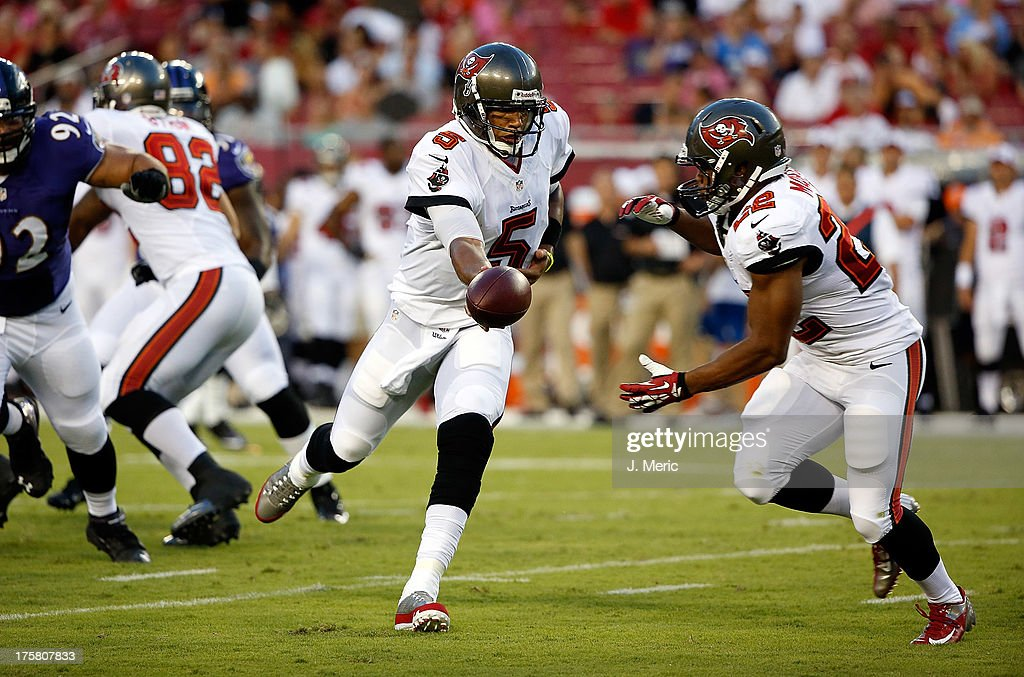 Quarterback <a gi-track='captionPersonalityLinkClicked' href=/galleries/search?phrase=Josh+Freeman&family=editorial&specificpeople=4036797 ng-click='$event.stopPropagation()'>Josh Freeman</a> #5 of the Tampa Bay Buccaneers hands the ball off to running back <a gi-track='captionPersonalityLinkClicked' href=/galleries/search?phrase=Doug+Martin+-+American+Football+Running+Back&family=editorial&specificpeople=9693143 ng-click='$event.stopPropagation()'>Doug Martin</a> #22 in the first quarter against the Baltimore Ravens during a preseason game at Raymond James Stadium on August 8, 2013 in Tampa, Florida.