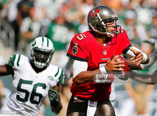 Quarterback Josh Freeman of the Tampa Bay Buccaneers is chased by linebacker DeMario Davis of the New York Jets as he looks to pass during a game at...