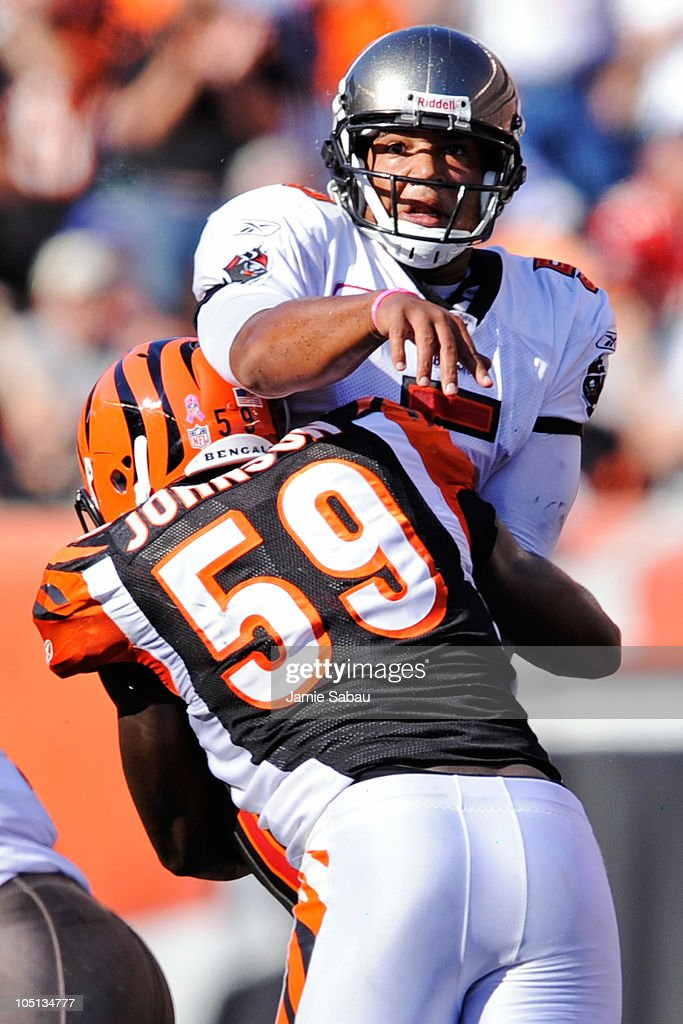 Quarterback <a gi-track='captionPersonalityLinkClicked' href=/galleries/search?phrase=Josh+Freeman&family=editorial&specificpeople=4036797 ng-click='$event.stopPropagation()'>Josh Freeman</a> #5 of the Tampa Bay Buccaneers is hit by Brandon Johnson #59 of the Cincinnati Bengals just as he releases the ball at Paul Brown Stadium on October 10, 2010 in Cincinnati, Ohio.