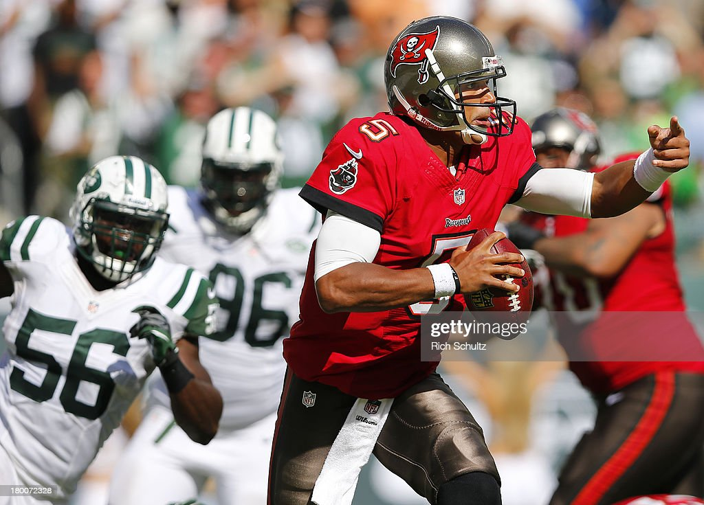 Quarterback <a gi-track='captionPersonalityLinkClicked' href=/galleries/search?phrase=Josh+Freeman&family=editorial&specificpeople=4036797 ng-click='$event.stopPropagation()'>Josh Freeman</a> #5 of the Tampa Bay Buccaneers is under pressure from linebacker DeMario Davis #56 and defensive end <a gi-track='captionPersonalityLinkClicked' href=/galleries/search?phrase=Muhammad+Wilkerson&family=editorial&specificpeople=7542316 ng-click='$event.stopPropagation()'>Muhammad Wilkerson</a> #96 of the New York Jets during the fourth quarter of a game at MetLife Stadium on September 8, 2013 in East Rutherford, New Jersey. The Jets defeated the Bucs 18-17.