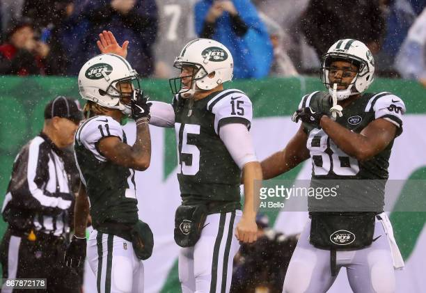 quarterback Josh McCown and tight end Austin SeferianJenkins of the New York Jets congratulate teammate wide receiver Robby Anderson on his touchdown...