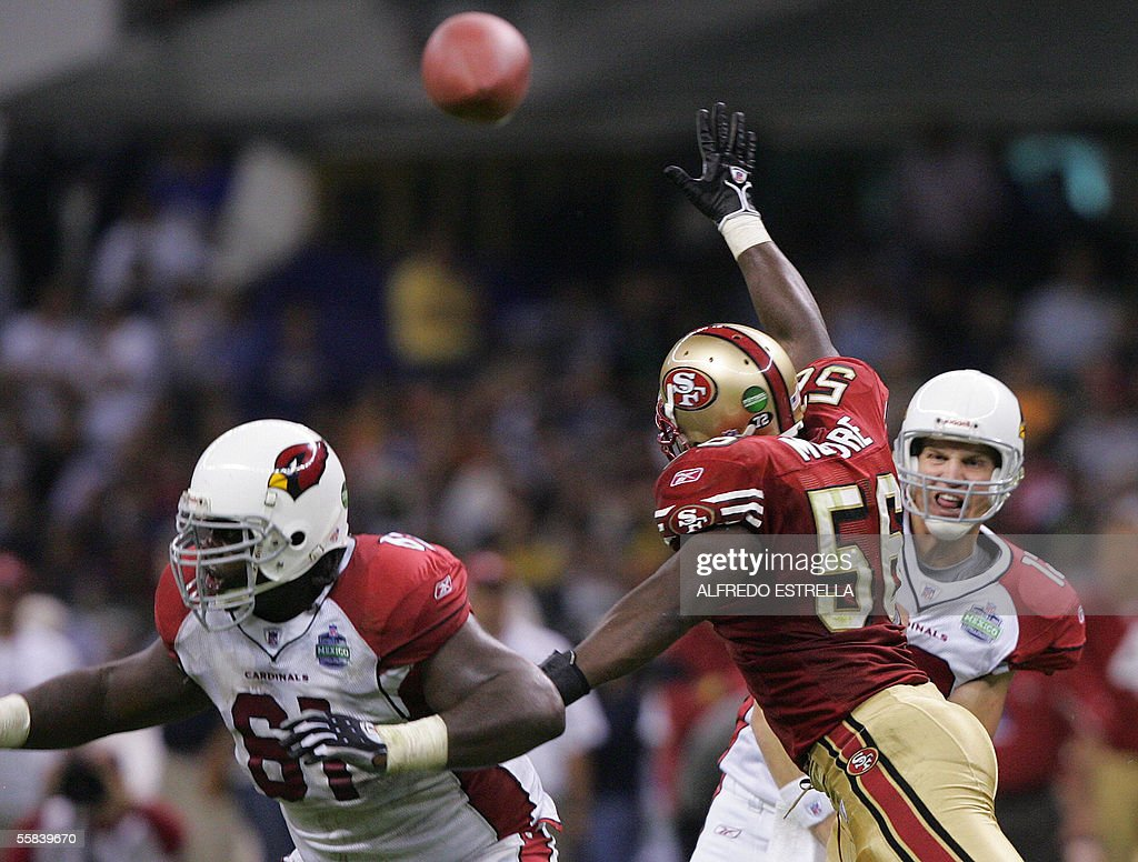 Quarterback Josh McCown #12 of Arizona Cardinals throws forward as Elton Brown #61 blocks Brandon Moore #56 of the San Francisco 49ers 02 October, 2005 at the Azteca stadium in Mexico City during the NFL first regular-season game. AFP PHOTO/Alfredo ESTRELLA