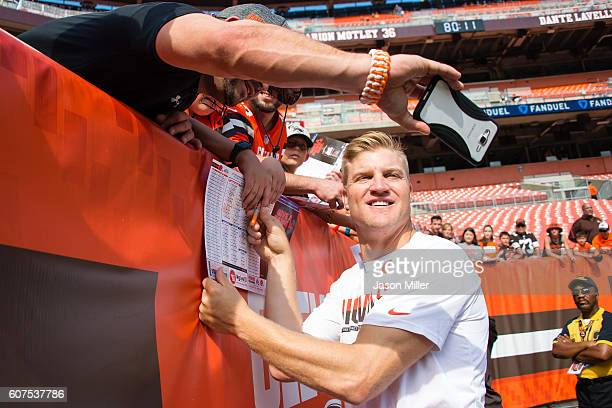 Quarterback Josh McCown of the Cleveland Browns poses for a photo with a fan prior to the game against the Baltimore Ravens at FirstEnergy Stadium on...
