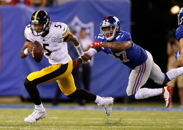 cf2d3d1ce8a ... Quarterback Joshua Dobbs 5 of the Pittsburgh Steelers escapes the grasp  of Valentino Blake Nike ...