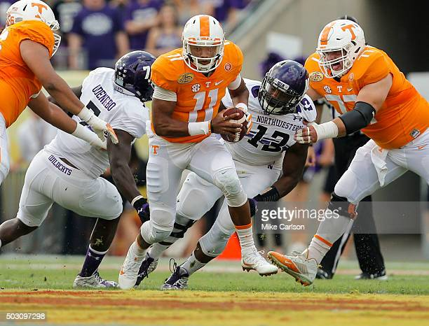 Quarterback Joshua Dobbs of the Tennessee Volunteers runs through the defense of Ifeadi Odenigbo and Deonte Gibson of the Northwestern Wildcats...