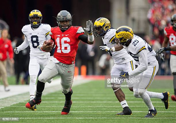 Quarterback JT Barrett of the Ohio State Buckeyes attempts to escape the defenders while running the ball during an NCAA football game between the...
