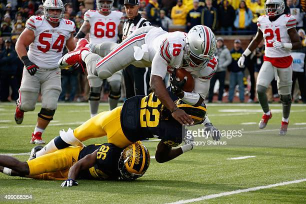 Quarterback JT Barrett of the Ohio State Buckeyes dives over Jarrod Wilson and Jourdan Lewis of the Michigan Wolverines for a third quarter touchdown...