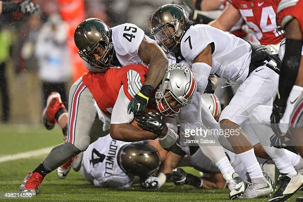 Quarterback JT Barrett of the Ohio State Buckeyes is brought down at the line of scrimmage by Darien Harris of the Michigan State Spartans and...