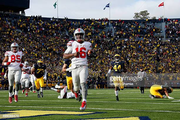 Quarterback JT Barrett of the Ohio State Buckeyes rushes for a fourth quarter touchdown against the Michigan Wolverines at Michigan Stadium on...