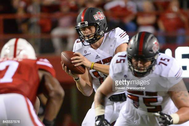 Quarterback Justice Hansen of the Arkansas State Red Wolves takes a snap against the Nebraska Cornhuskers at Memorial Stadium on September 2 2017 in...