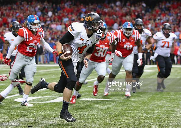 Quarterback JW Walsh of the Oklahoma State Cowboys rushes for a touchdown against the Mississippi Rebels during the fourth quarter of the Allstate...