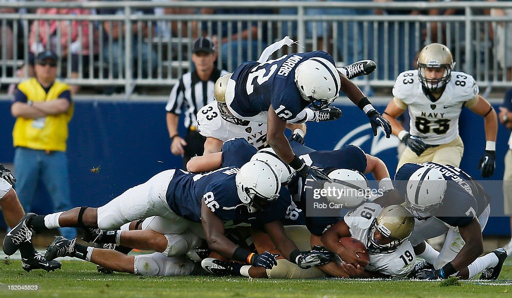 Quarterback Keenan Reynolds of the Navy Midshipmen is stopped by the Penn State Nittany Lions defense during the second half at Beaver Stadium on...