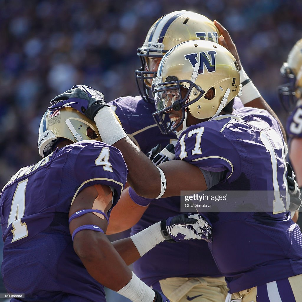 Quarterback Keith Price #17 of the Washington Huskies celebrates with teammates after rushing for a touchdown against the Idaho State Bengals on September 21, 2013 at Husky Stadium in Seattle, Washington. The score gave the Huskies a 26-0 lead in the first half.