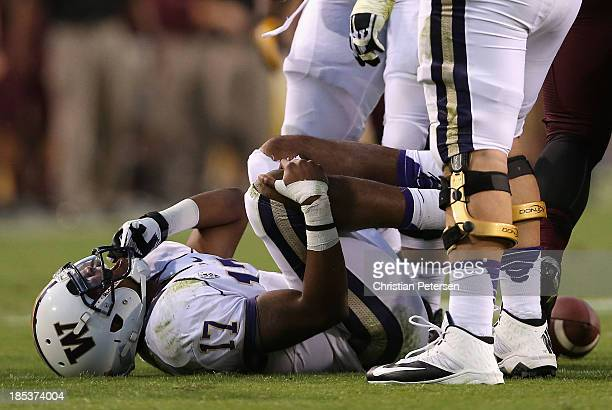Quarterback Keith Price of the Washington Huskies grabs his leg after an injury during the fourth quarter of the college football game against the...