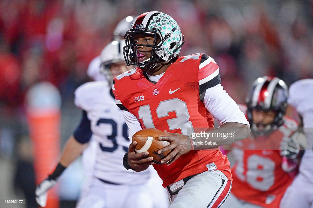 Quarterback <a gi-track='captionPersonalityLinkClicked' href=/galleries/search?phrase=Kenny+Guiton&family=editorial&specificpeople=6513927 ng-click='$event.stopPropagation()'>Kenny Guiton</a> #13 of the Ohio State Buckeyes runs for an 11-yard touchdown in the fourth quarter against the Penn State Nittany Lions at Ohio Stadium on October 26, 2013 in Columbus, Ohio. Ohio State defeated Penn State 63-14.