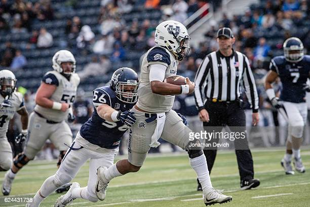 Quarterback Kent Myers of the Utah State Aggies gets away from linebacker Alex Bertrand to run for a touchdown against the Nevada Wolf Pack at Mackay...