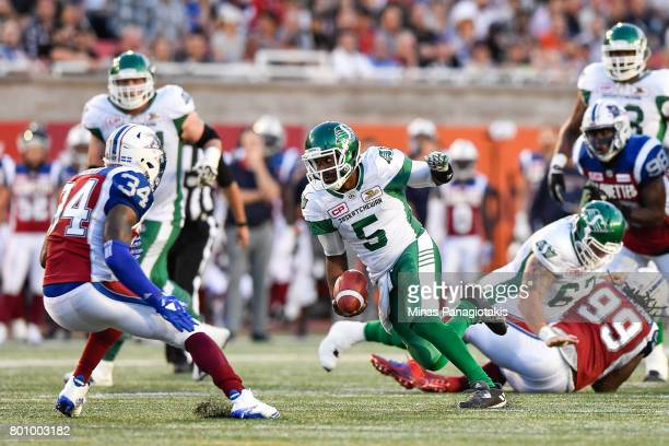 Quarterback Kevin Glenn of the Saskatchewan Roughriders runs with the ball near linebacker Kyries Hebert of the Montreal Alouettes during the CFL...