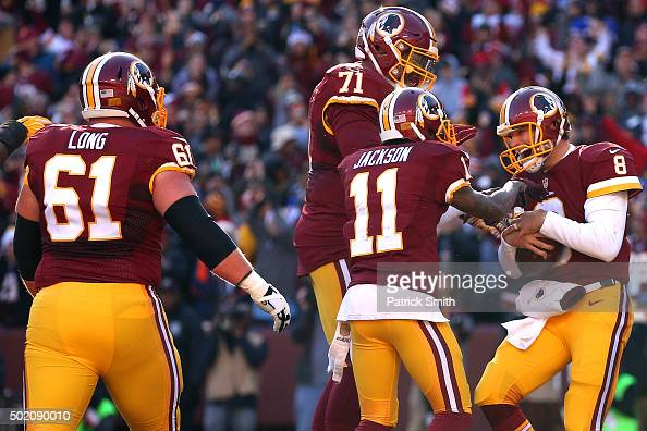 Quarterback Kirk Cousins of the Washington Redskins celebrates with teammates after scoring a second quarter touchdown against the Buffalo Bills at...