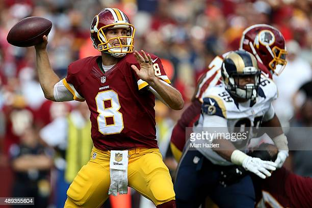 Quarterback Kirk Cousins of the Washington Redskins drops back to pass while defensive tackle Aaron Donald of the St Louis Rams defends in the third...