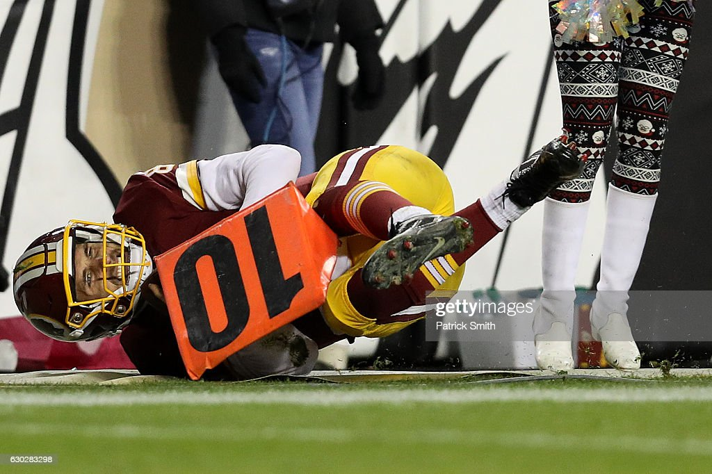 Quarterback Kirk Cousins #8 of the Washington Redskins is pushed out of bounds in the fourth quarter against the Carolina Panthers at FedExField on December 19, 2016 in Landover, Maryland.