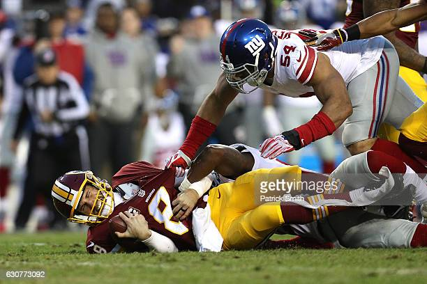 Quarterback Kirk Cousins of the Washington Redskins is sacked by defensive end Olivier Vernon and strong safety Landon Collins of the New York Giants...