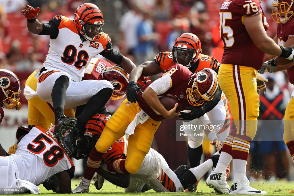 Quarterback Kirk Cousins #8 of the Washington Redskins is sacked by defensive end Chris Smith #94 and defensive end Wallace Gilberry #95 of the Cincinnati Bengals in the first quarter during a preseason game at FedExField on August 27, 2017 in Landover, Maryland.