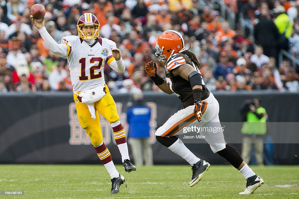 Quarterback <a gi-track='captionPersonalityLinkClicked' href=/galleries/search?phrase=Kirk+Cousins&family=editorial&specificpeople=5571638 ng-click='$event.stopPropagation()'>Kirk Cousins</a> #12 of the Washington Redskins passes under pressure from defensive end Jabaal Sheard #97 of the Cleveland Browns during the second half at Cleveland Browns Stadium on December 16, 2012 in Cleveland, Ohio. The Redskins defeated the Browns 38-21.