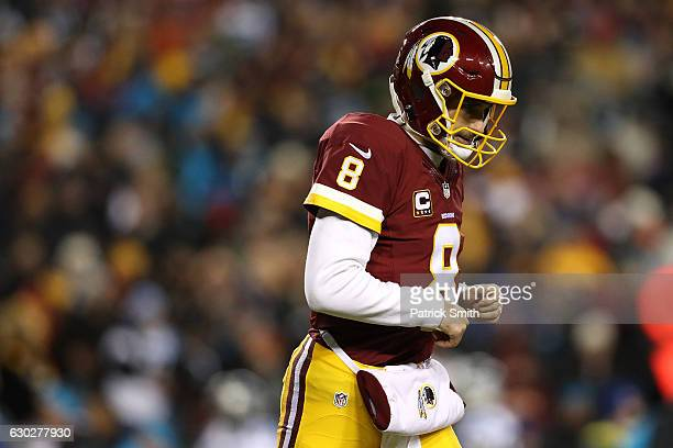 Quarterback Kirk Cousins of the Washington Redskins runs off of the field after throwing an interception against the Carolina Panthers in the first...