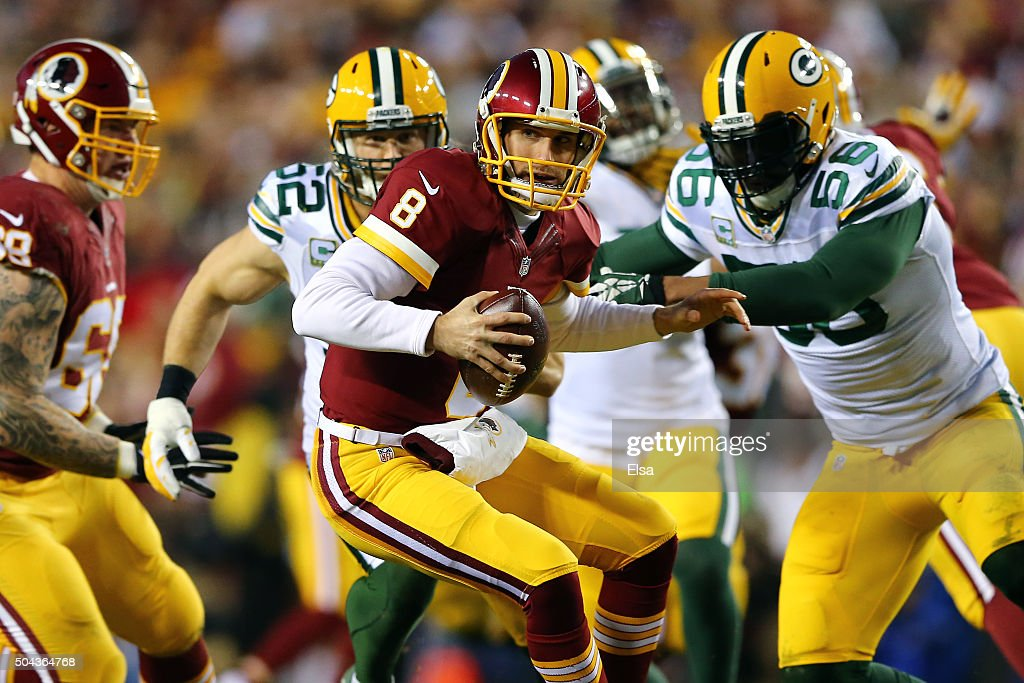 Quarterback Kirk Cousins of the Washington Redskins scrambles under pressure by outside linebacker Julius Peppers of the Green Bay Packers in the...