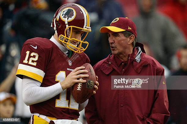 Quarterback Kirk Cousins of the Washington Redskins talks with head coach Mike Shanahan during warmups prior to playing an NFL game against the...