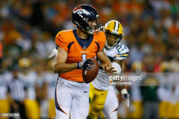 Quarterback Kyle Sloter of the Denver Broncos runs from safety Josh Jones of the Green Bay Packers in the fourth quarter of a Preseason game at...