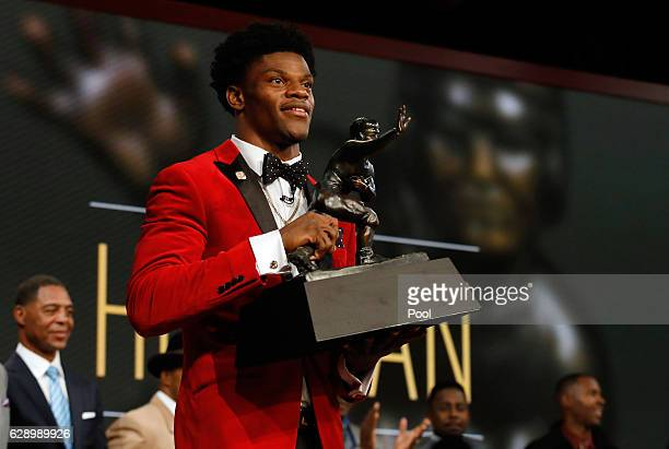 Quarterback Lamar Jackson of the Louisville Cardinals poses with the trophy after being named the 82nd Heisman Memorial Trophy Award winner during...