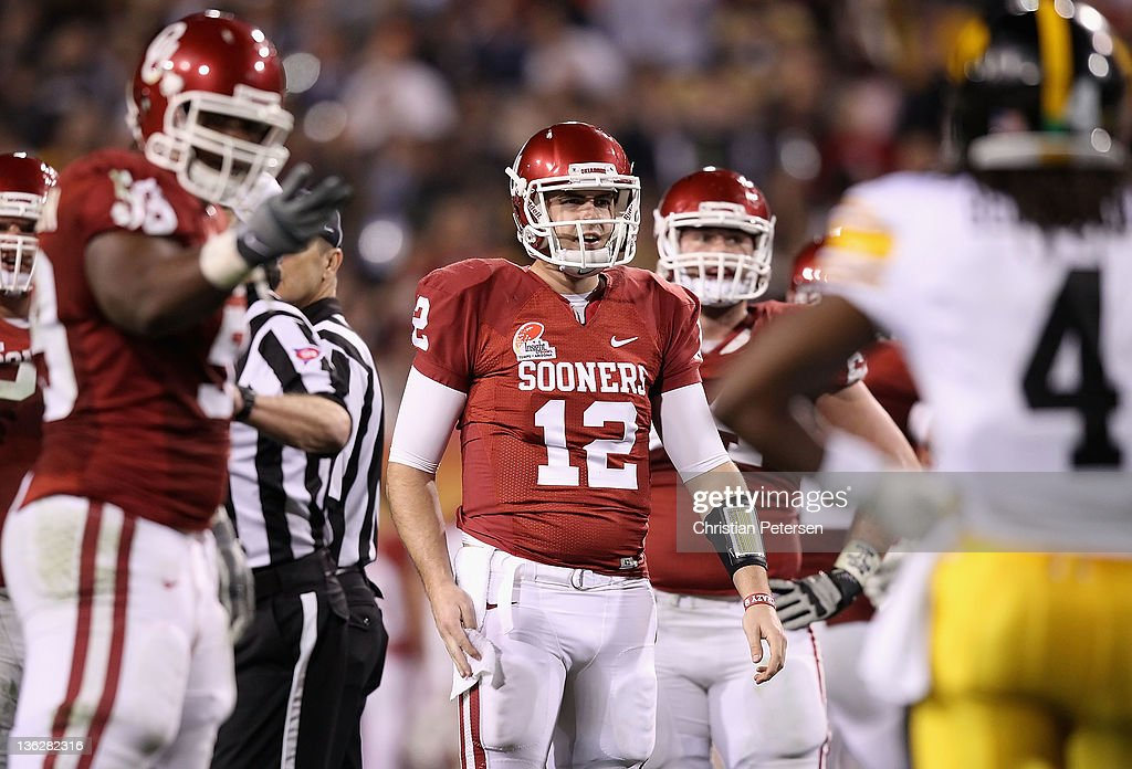 Quarterback <a gi-track='captionPersonalityLinkClicked' href=/galleries/search?phrase=Landry+Jones&family=editorial&specificpeople=5572476 ng-click='$event.stopPropagation()'>Landry Jones</a> #12 of the Oklahoma Sooners reacts after being hit by defenisve back Jordan Bernstine #4 (R) of the Iowa Hawkeyes during the second quarter of the Insight Bowl at Sun Devil Stadium on December 30, 2011 in Tempe, Arizona.