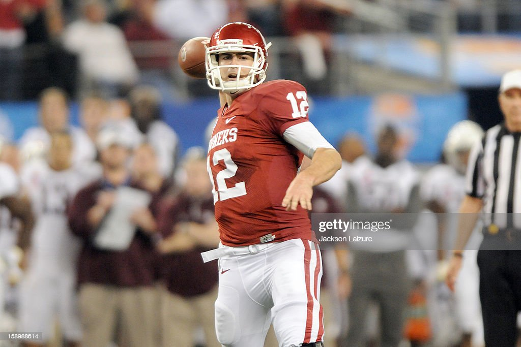 Quarterback Landry Jones #12 of the Oklahoma Sooners throws a first-half pass against the Texas A&M Aggies on January 4, 2012 at the Cotton Bowl at Cowboys Stadium in Arlington, Texas.