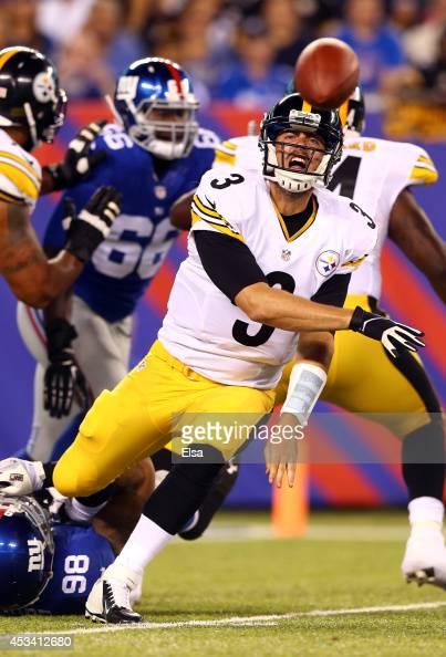 Quarterback Landry Jones of the Pittsburgh Steelers makes a throw as he is tackled by defensive end Damontre Moore of the New York Giants during a...