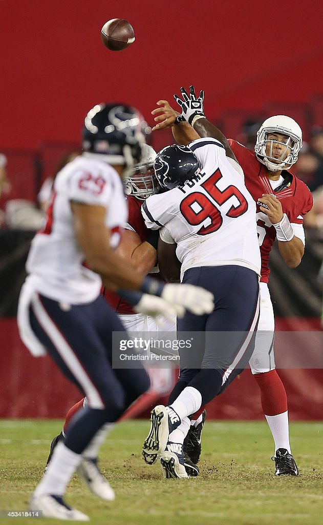 Quarterback Logan Thomas of the Arizona Cardinals throws a pass under pressure from nose tackle Jerrell Powe of the Houston Texans during the fourth...