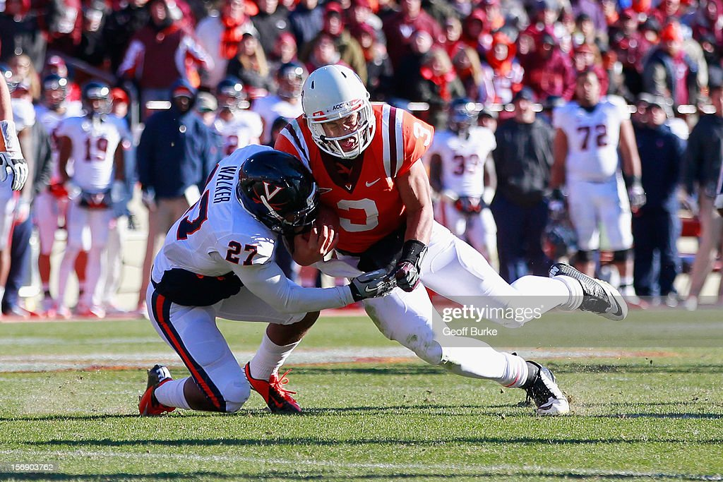 Quarterback <a gi-track='captionPersonalityLinkClicked' href=/galleries/search?phrase=Logan+Thomas&family=editorial&specificpeople=6787143 ng-click='$event.stopPropagation()'>Logan Thomas</a> #3 of the Virginia Tech Hokies runs with the ball as safety Rijo Walker #27 of the Virginia Cavaliers makes the tackle at Lane Stadium on November 24, 2012 in Blacksburg, Virginia.