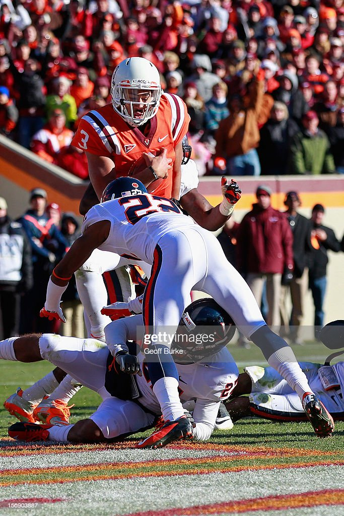 Quarterback <a gi-track='captionPersonalityLinkClicked' href=/galleries/search?phrase=Logan+Thomas&family=editorial&specificpeople=6787143 ng-click='$event.stopPropagation()'>Logan Thomas</a> #3 of the Virginia Tech Hokies runs with the ball to score a touchdown as safety Rijo Walker #27 of the Virginia Cavaliers and cornerback Drequan Hoskey #22 of the Cavaliers defend at Lane Stadium on November 24, 2012 in Blacksburg, Virginia.