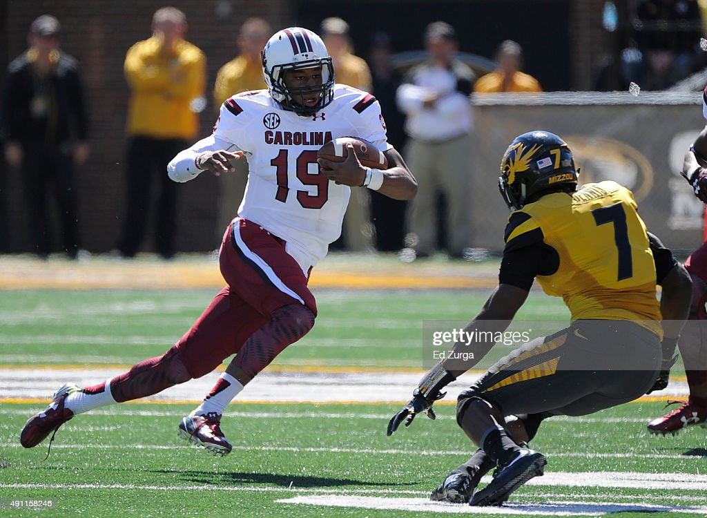 Quarterback Lorenzo Nunez #19 of the South Carolina Gamecocks tries to make his way past Kenya Dennis #7 of the Missouri Tigers in the third quarter at Memorial Stadium on October 3, 2015 in Columbia, Missouri.