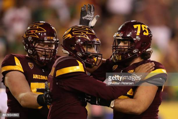 Quarterback Manny Wilkins of the Arizona State Sun Devils celebrates with offensive lineman Tyler McClure after scoring on a two yard rushing...