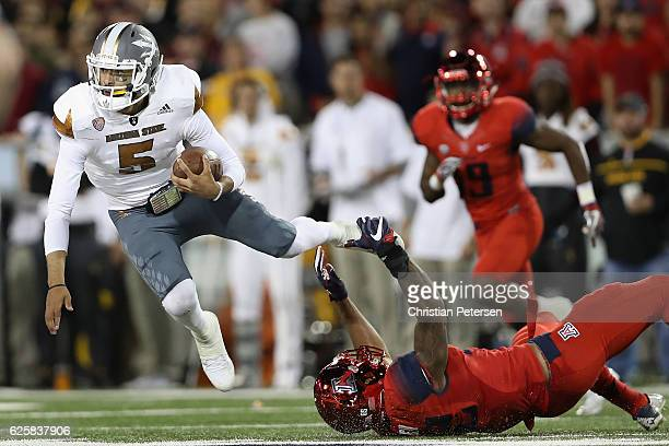 Quarterback Manny Wilkins of the Arizona State Sun Devils is tackled by linebacker DeAndre' Miller of the Arizona Wildcats during the third quarter...