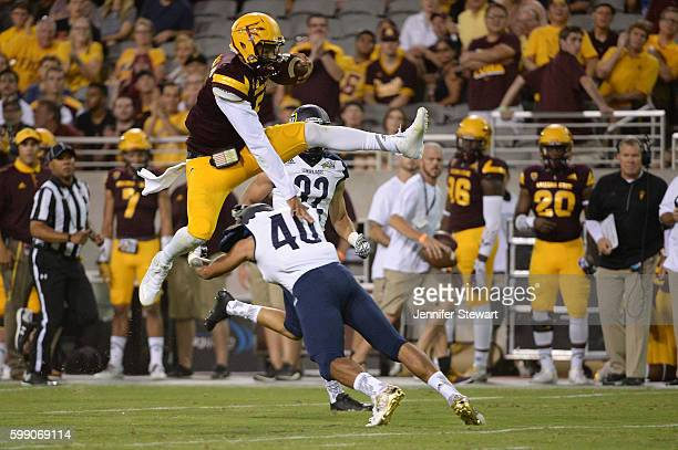 Quarterback Manny Wilkins of the Arizona State Sun Devils leaps over safety Keith Graham of the Northern Arizona Lumberjacks while running the ball...