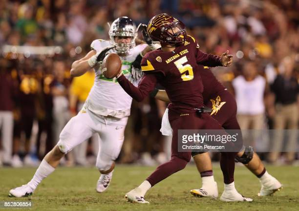 Quarterback Manny Wilkins of the Arizona State Sun Devils throws a pass under pressure from defensive lineman Henry Mondeaux of the Oregon Ducks...