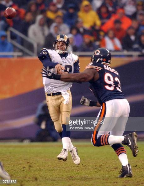Quarterback Marc Bulger of the St Louis Rams throws the ball under pressure from lineman Phillip Daniels of the Chicago Bears during a game on...