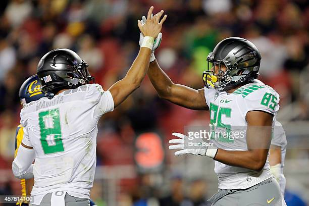 Quarterback Marcus Mariota and tight end Pharoah Brown of the Oregon Ducks high five after connecting for a touchdown catch against the California...
