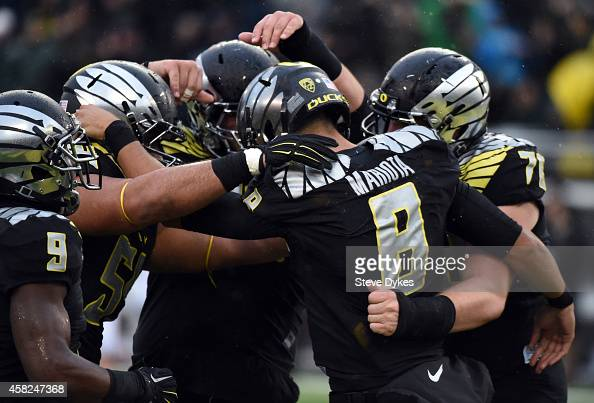 Quarterback Marcus Mariota of the Oregon Ducks celebrates with his teammates after scoring a touch down during the first quarter of the game against...